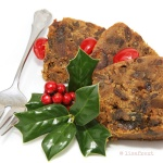 three slices of dark fruitcake with grandma's silver fork and a sprig of holly