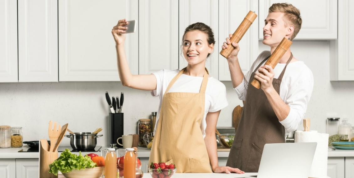 Young woman and man wearing kitchen aprons with pockets